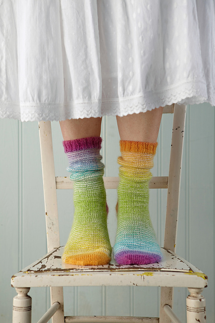 knitting multicoloured socks standing on vintage chair blue background white skirt