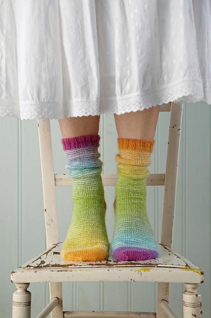 knitting multicoloured socks standing on vintage chair blue background white skirt